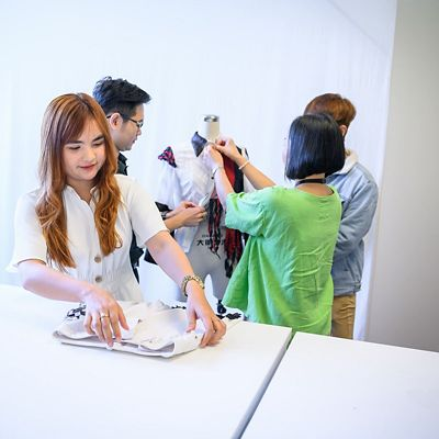 People in a fashion studio dressing a model.