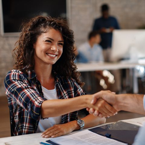 Woman shaking hand over business agreement.