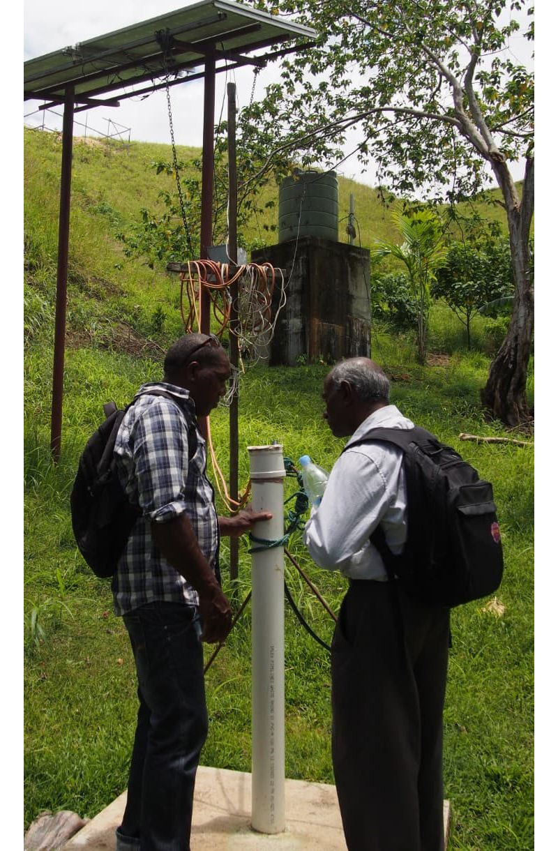 RMIT academic Jega Jegatheesan inspects a borehole with a local community member.