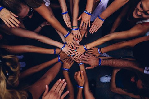 A group of people placing their hands on top of each other in a circle.