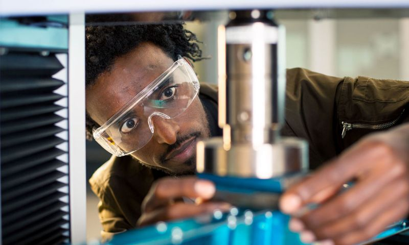 A man works on an engineering project holding an instrument with safety glasses.