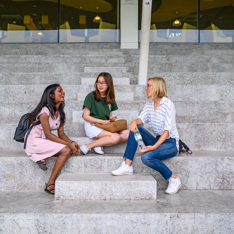 3 international students - Vietnamese, Danish and Sri Lankan, sitting on bleachers having a chat