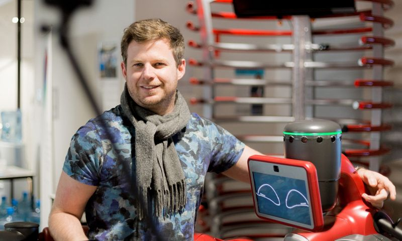 Man wearing scarf stands with arm on robot