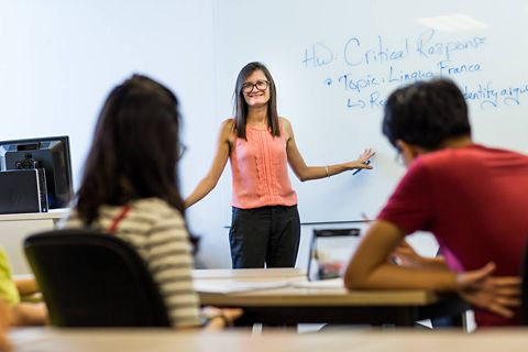 English teacher in class at whiteboard with students in attendance