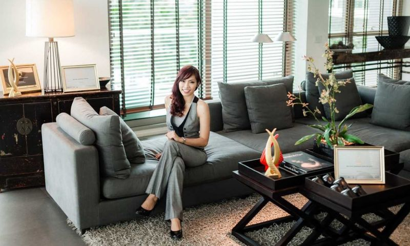 Woman sits on grey sofa in apartment