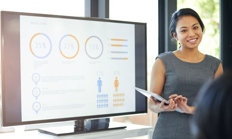 Woman stands next to HR presentation on screen