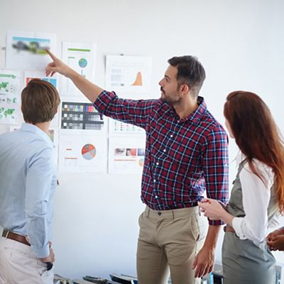 A group of people planning a project with information on the wall