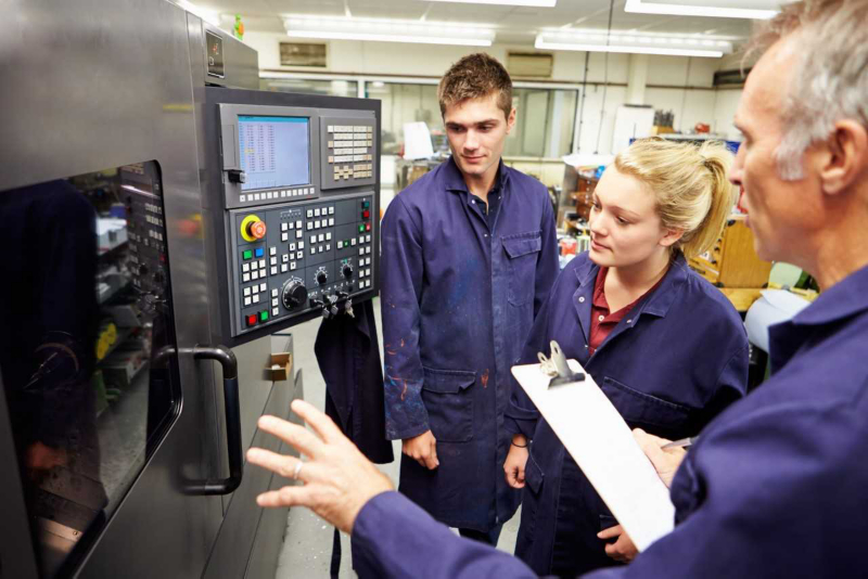 Students learning how to operate a machine